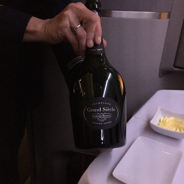American Airlines Flight Attendant displaying Laurent-Perrier Grand Siecle Champagne with pride